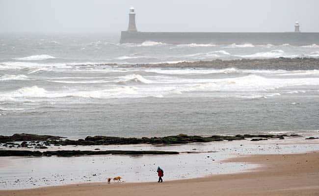 A man walks on Tynemouth Beach near Newcastle as the hot weather turns to rainy and windy conditions across many parts of the UK./Owen Humphreys/PA Archive/PA Images