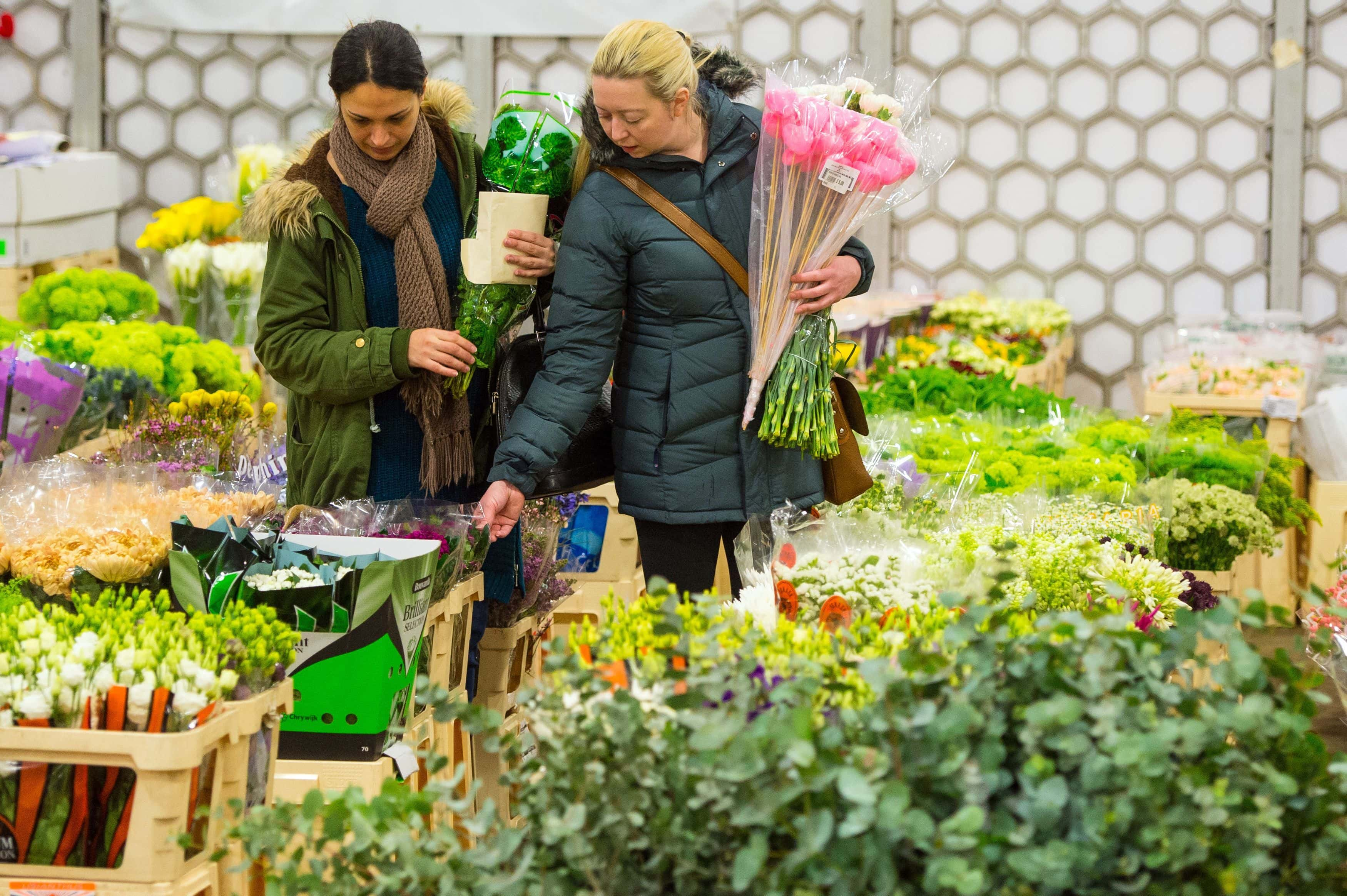 Two women browse produce at New Covent Garden Flower Market, which is the UK's largest wholesale flower market, in Nine Elms, London, ahead of Mothering Sunday this weekend.