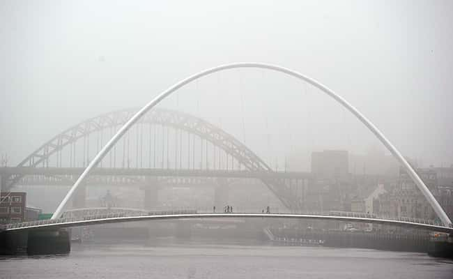 Photo: People walk through fog to cross the Tyne Bridge in Newcastle upon Tyne./Picture by: Owen Humphreys / PA Archive/Press Association Images.