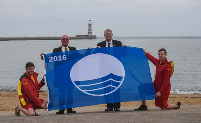 Councillor John Kelly, (3rd from left) Portfolio Holder for Public Health, Wellness and Culture, Sunderland City Council, with l-r Alexander Robinson lifeguard, Tom Parkin chairman Sunderland Seafront Traders Association and Phil Johnson lifeguard with the Blue Flag for Roker and Seaburn beaches.