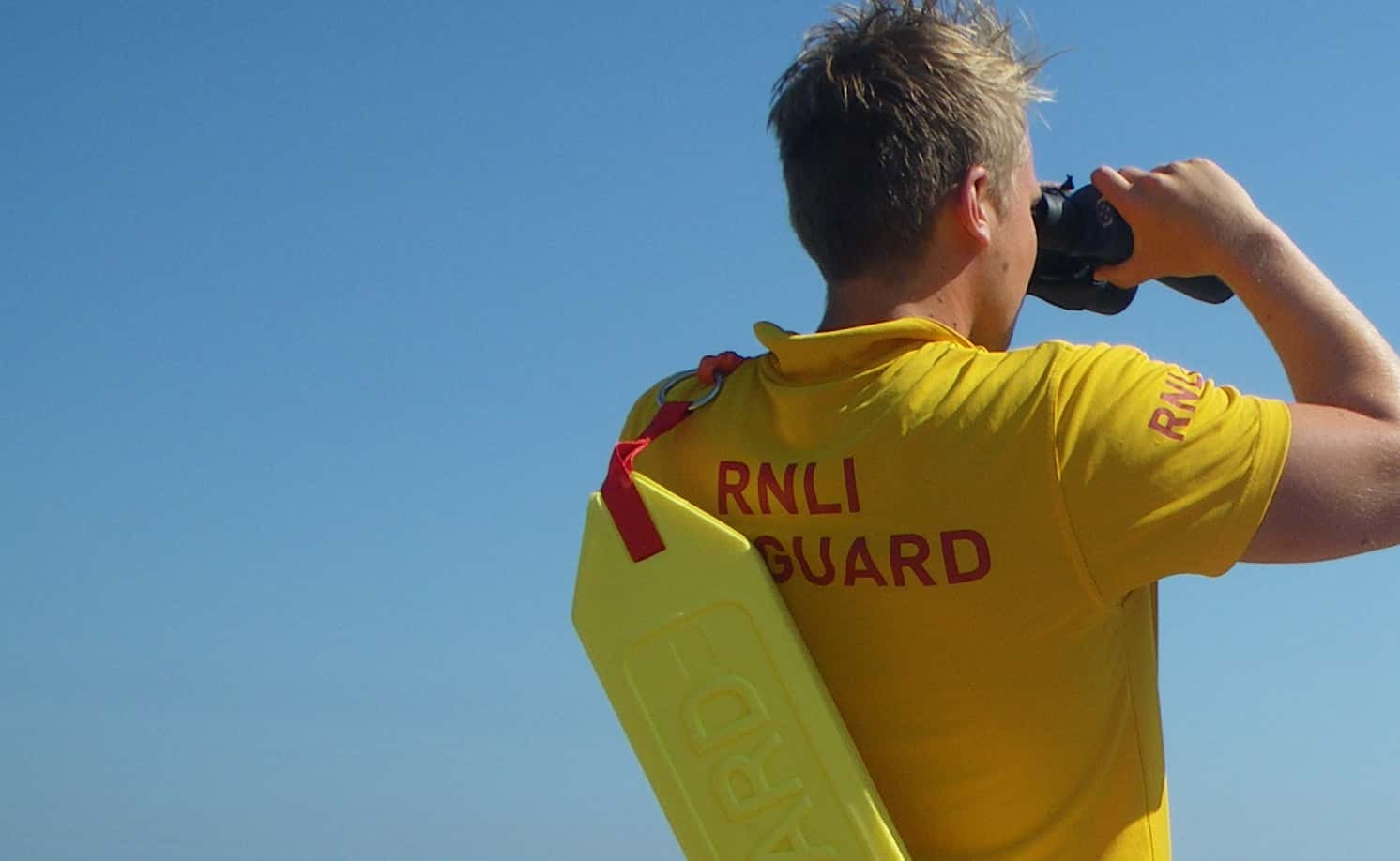The photograph shows an RNLI lifeguard on patrol/ RNLI.
