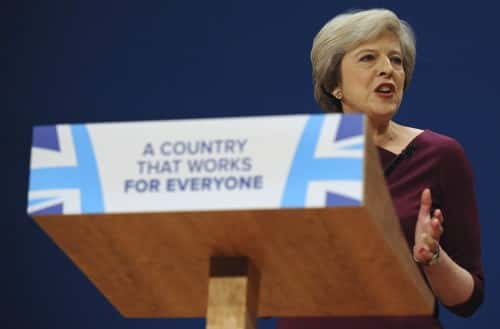 "Conservative Party Leader and Prime Minister, Theresa May, addresses delegates at the Conservative Party Conference at the ICC, in Birmingham, England, Wednesday, Oct. 5, 2016. May has vowed to govern from the ""center ground"" of politics, a day after her government alarmed liberals by saying that businesses should prioritize hiring British workers over foreign ones. (AP Photo/Rui Vieira)"