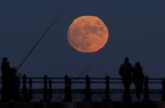 A fisherman fishes off Roker Pier in Sunderland as the waxing full moon rises.