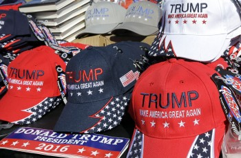 Campaign hats, books and bumper stickers for Republican presidential candidate Donald Trump sit on a table for sale outside a campaign rally, Friday, April 15, 2016, in Plattsburgh, N.Y. (AP Photo/Elise Amendola)