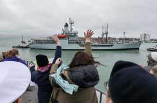 People wave as Royal Fleet Auxiliary Gold Rover passes the Round Tower as she enters Portsmouth Harbour flying a paying-off pennant at the end of 43 years in services in support of the Royal Navy.