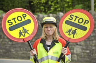 lollipop lady Helen Tilbury compares an old (right) and new hi-tech lollipop stick (left), which has CCTV video built-in to capture any motorists who break the law or become aggressive.