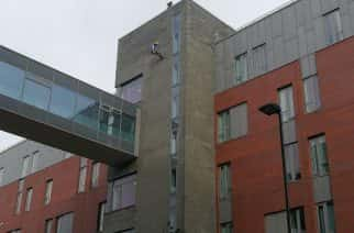 15 people abseil down 97-feet block for charity