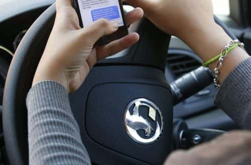 PICTURE POSED BY MODEL File photo dated 13/08/14 of a woman texting on her phone whilst driving, as Department for Transport figures suggest young people are nearly twice as likely to use a mobile phone while driving.
