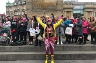 Newcastle flash mob turns Monument red for International Women's Day