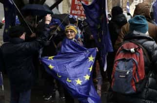 An anti-Brexit remain in the European Union supporter holds a European Union flag during a protest outside the Houses of Parliament in London, Tuesday, March 12, 2019. Britain's attorney general punctured Prime Minister Theresa May's hopes of winning backing for her Brexit deal Tuesday, saying last-minute changes secured from the European Union didn't give Britain the power to cut itself free of ties to the bloc. (AP Photo/Matt Dunham)