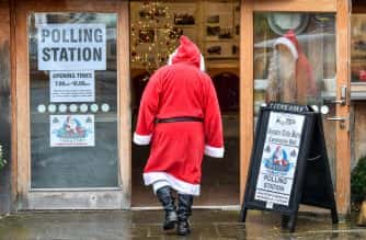 PA Images: A man dressed as Father Christmas enters his grotto at the Dunster Tithe Barn near Minehead, Somerset, which is being used as a polling station in the 2019 General Election.