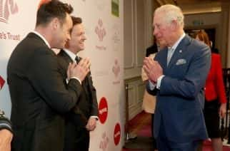 """File photo dated 11/03/20 of the Prince of Wales using a Namaste gesture to greet television presenters Ant McPartlin (left)and Declan Donnelly as he arrives at the annual Prince's Trust Awards 2020 held at the London Palladium. The Prince of Wales has tested positive for coronavirus and is displaying mild symptoms """"but otherwise remains in good health"""", Clarence House has said."""