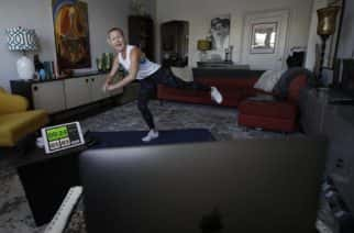 Shane Barnard, CEO of UrbanKick, shows participants on her computer in the HIIT and Core class how to perform a workout from her home in Oakland, Calif., Thursday, March 26, 2020. Barnard started livestreaming workouts on Wednesday, March 18, 2020, after losing her job as a trainer at a gym due to shelter-in-place orders from coronavirus concerns. Barnard does not charge for her classes, but accepts donations, and says she averages around 100 participants per class. (AP Photo/Jeff Chiu)