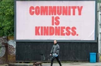 A man walks a dog beneath a billboard reading 'community is kindness', in south London, as the UK continues in lockdown to help curb the spread of coronavirus.