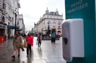 """People wearing face masks walk past a hand sanitiser station in a near-deserted Piccadilly Circus in London, England, on October 15, 2020. London is to be placed under """"Tier 2"""" coronavirus lockdown measures from this weekend, which will introduce a ban on people from different households from mixing anywhere indoors, spelling particular concern for the already badly-affected hospitality industry. Several other parts of the country are also to see their covid-19 restrictions similarly stepped-up. The three-tier system for England came into effect this week, with each area of the country classed as being on a medium, high or very high alert (otherwise known as Tiers 1 to 3). (Photo by David Cliff/NurPhoto)"""