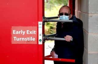 A football fan is seen entering a ground through the turnstiles whilst wearing a face mask.