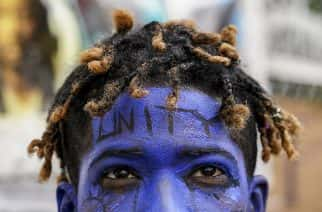A demonstrator going by the name Azul Azul walks around with a painted face outside the White House, in Washington.  AP Photo: John Minchillo