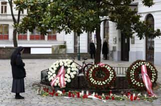 A nun stands at the crime scene besides wreaths and candles in Vienna, Austria, Wednesday, Nov. 4, 2020. Several shots were fired shortly after 8 p.m. local time on Monday, Nov. 2, in a lively street in the city center of Vienna. (AP Photo/Matthias Schrader)