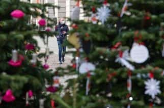 A man wearing a face mask is seen amongst Christmas trees in Covent Garden, London, as England continues a four week national lockdown to curb the spread of coronavirus.