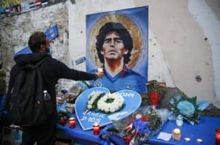 "A man holds a candle as people gather to honor soccer legend Diego Maradona, at the popular ""Quartieri Spagnoli"" neighborhood, in Naples, Thursday, Nov. 26, 2020. Maradona died on Wednesday at the age of 60 of a heart attack in a house outside Buenos Aires where he recovered from a brain operation. (AP Photo/Alessandra Tarantino)"