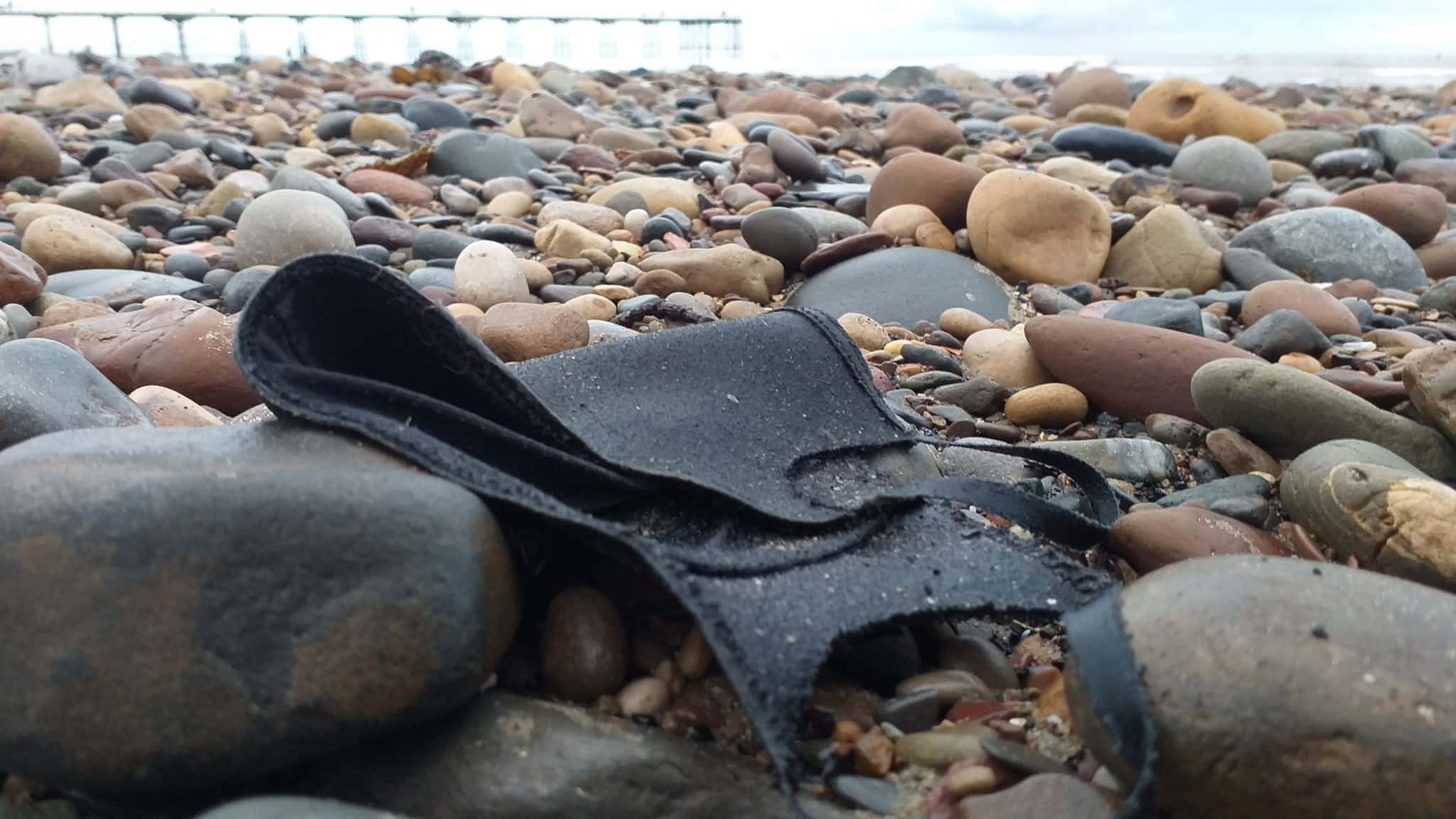 Photo of discarded black face mask on beach