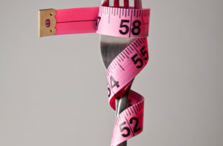 D9P9CW A single silver fork with pink measuring tape wrapped around it relating to a strict diet or healthy eating plan.